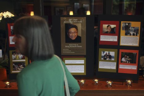 A woman walks past an informational booth detailing the life of Kenneth Bae during a vigil for Bae in Seattle, Washington August 10, 2013. R