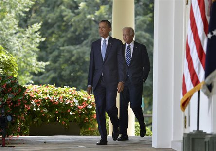 U.S. President Barack Obama walks with Vice President Joe Biden (R) to the Rose Garden of the White House to make remarks on the situation i