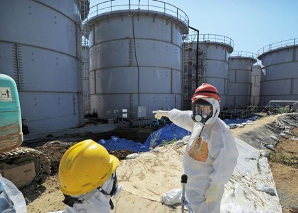 Japan's Economy, Trade and Industry Minister Toshimitsu Motegi (R), wearing a protective suit and a mask, inspects contaminated water tanks