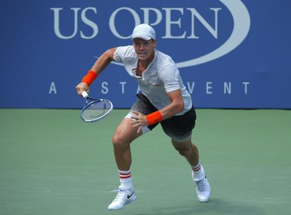 Tomas Berdych of the Czech Republic runs to the net for a return from Julien Benneteau of France at the U.S. Open tennis championships in Ne