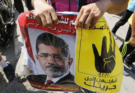 "Supporters of ousted Egyptian president Mohamed Mursi hold his picture and a poster (R) showing the ""Rabaa"" or ""four"" gesture, in reference"