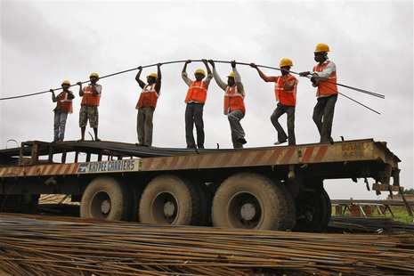 Workers unload iron rods from a truck at the construction site of an educational institute on the outskirts of western Indian city of Ahmeda