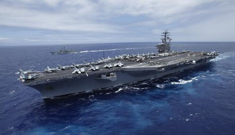 The USS Nimitz, a nuclear-powered aircraft carrier which is currently supplemented by biofuel, sails about 150 miles north of the island of
