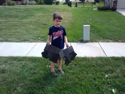 Five-year-old Lex Anderson holds shingles blown off the roof of houses in his neighborhood. (KELO AM photo)