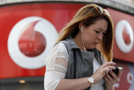 A woman talks on her mobile phone as she walks past a Vodafone store in London September 2, 2013 REUTERS/Stefan Wermuth
