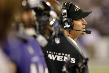 Baltimore Ravens head coach John Harbaugh (R) watches from the sideline during the first half of their NFL pre-season football game against