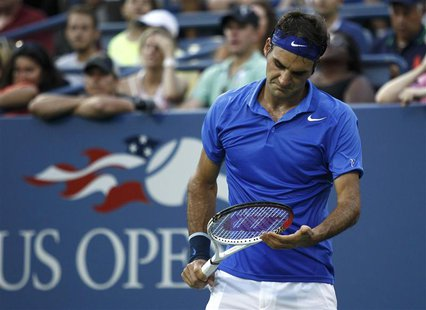 Roger Federer of Switzerland looks down at his racquet during the second set against Tommy Robredo of Spain at the U.S. Open tennis champion
