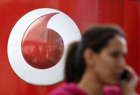 A woman talks on her mobile phone as she walks past a Vodafone store in London September 2, 2013. REUTERS/Stefan Wermuth