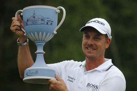 Henrik Stenson of Sweden poses with the trophy after winning the 2013 Deutsche Bank Championship golf tournament in Norton, Massachusetts Se