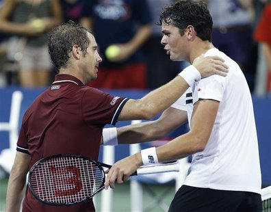 Milos Raonic of Canada (R) congratulates Richard Gasquet of France after Gasquet's win at the U.S. Open tennis championships in New York, Se