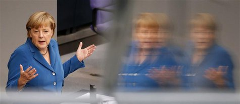 German Chancellor Angela Merkel is reflected in a window as she gives a speech during a debate of the lower house of parliament Bundestag in