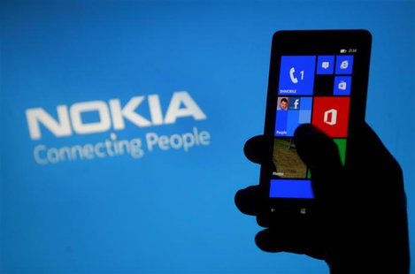 A woman poses with a Nokia Lumia smartphone in the central Bosnian town of Zenica, in this May 6, 2013 file illustration photograph. REUTERS