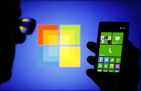 A man is silhouetted against a video screen with as he poses with a Nokia Lumia 820 smartphone in this photo illustration taken in the centr
