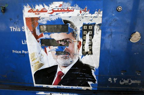 The remnants of a poster of ousted Egyptian President Mohamed Mursi are seen at a petrol station in Cairo August 28, 2013. REUTERS/Louafi La