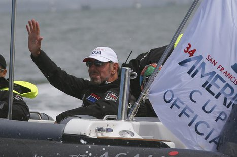 Oracle Corporation co-founder and CEO Larry Ellison waves to a passing boat prior to the first race of the Louis Vuitton Cup challenger seri