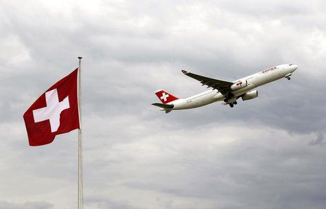 An Airbus A 330-343E of Swiss airlines takes-off past a Swiss national flag from the airport in Zurich October 4, 2012. REUTERS/Arnd Wiegman