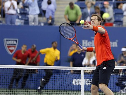 Security runs onto the court as Andy Murray of Britain hits a ball into the crowd to celebrate defeating Denis Istomin of Uzbekistan at the