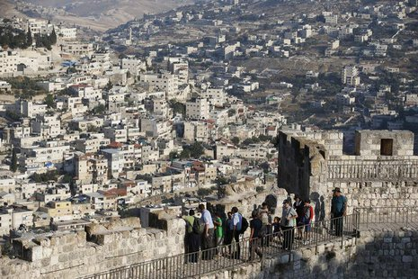Arab neighbourhoods in East Jerusalem are seen in the background as tourists walk atop a wall surrounding Jerusalem's Old City August 13, 20