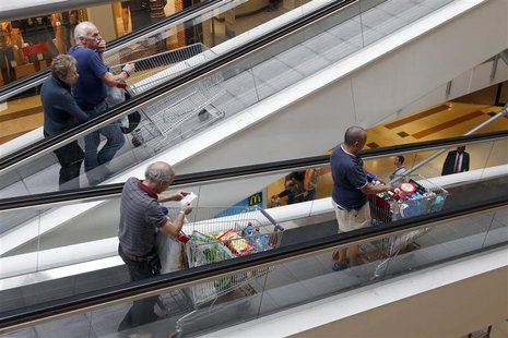 Customers push shopping trolleys on an escalator at the Bercy shopping centre in Charenton Le Pont, near Paris, August 29, 2013. REUTERS/Cha
