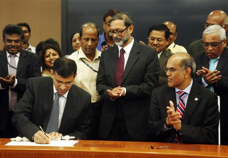 Raghuram Rajan (L), newly appointed governor of Reserve Bank of India (RBI), signs papers during the taking over ceremony at the bank's head