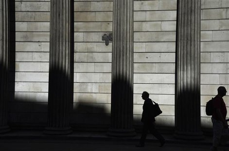 Workers walk past the Bank of England in the City of London August 7, 2013. REUTERS/Toby Melville