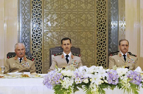 Syria's President Bashar al-Assad (C) attends a dinner in honor of the army officers on the 65th Army Foundation anniversary in Damascus Aug