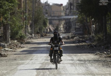 A fighter from the Islamist Syrian rebel group Jabhat al-Nusra rides a motorcycle along a deserted street in Deir al-Zor August 17, 2013. RE