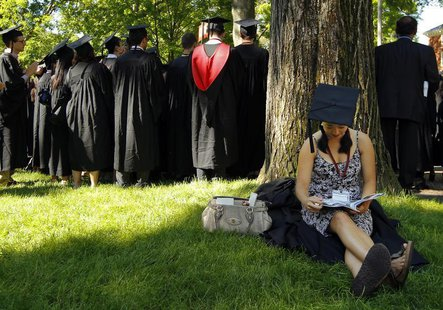 Graduating student Jennifer Lim sits in the shade before the start of the 361st Commencement Exercises at Harvard University in Cambridge, M