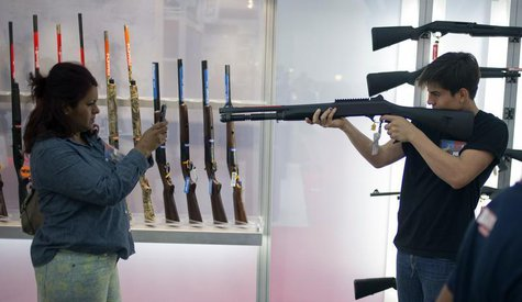 A woman uses a smart phone to photograph a young man holding a shotgun at an exhibit booth at the George R. Brown convention center, the sit