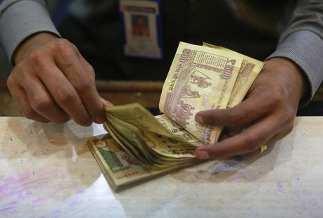 A cashier counts Indian rupee currency notes inside a bank in Mumbai August 5, 2013. REUTERS/Danish Siddiqui