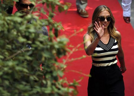 "Actress Scarlett Johansson waves as she arrives for a news conference for the movie ""Under the Skin"", directed by Jonathan Glazer, during th"