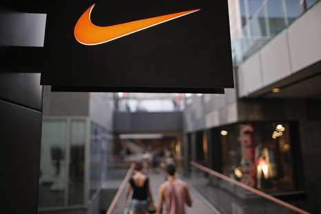 People walks past a Nike shop under the company logo at the Sanlitun shopping area in central Beijing, August 8, 2013. REUTERS/Petar Kujundz