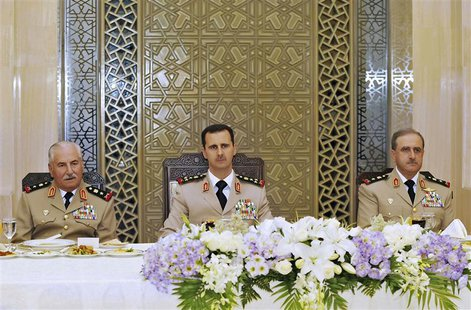 Syria's President Bashar al-Assad (C) attends a dinner with Defense Minister General Ali Habib (L) and Chief of Staff General Dawoud Rajhain