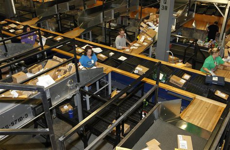 United Parcel Service employees sort packages at the UPS Worldport All Points International Hub during the peak delivery day in Louisville,