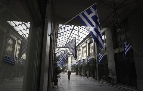 Greek flags are seen as a man walks inside an arcade with closed shops in central Athens October 26, 2012. REUTERS/John Kolesidis