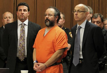 Ariel Castro (C), 53, stands between attorneys Craig Weintraub (L) and Jaye Schlachet as his sentence is read to him by judge Michael J. Rus