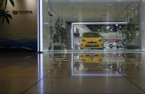 An employee of Toyota Motor Corp prepares to open the company's showroom in Nagoya, central Japan July 1, 2013. REUTERS/Toru Hanai