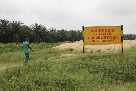 A man walks past a signboard erected along the right of way of Royal Dutch Shell in the Delta region August 6 2013. Reuters/Stringer