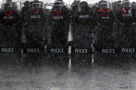 Heavy rain falls on policemen taking positions as rubber farmers protest near the airport in Surat Thani September 4, 2013. REUTERS/Athit Pe