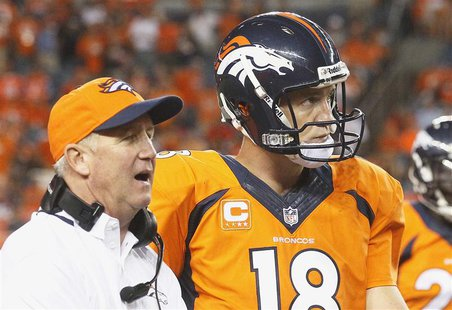 Denver Broncos quarterback Peyton Manning (R) listens to Broncos head coach John Fox late in the fourth quarter in their NFL football game a