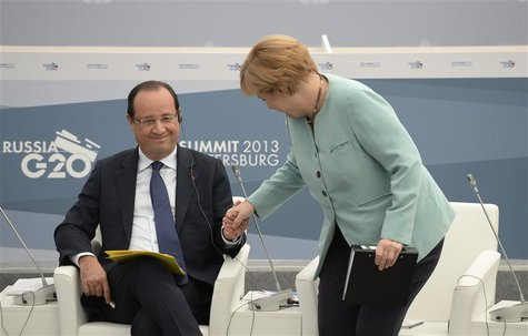 German Chancellor Angela Merkel (R) and French President Francois Hollande attend a meeting with business leaders in St.Petersburg September