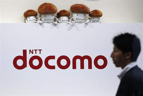 A man walks past the logo of Japan's biggest mobile phone operator NTT Docomo at its shop in Tokyo in this July 3, 2013 file photograph. REU