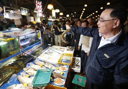 South Korea's Prime Minister Jung Hong-won holds up a domestic fish during his visit to the Noryangjin fisheries wholesale market in Seoul S