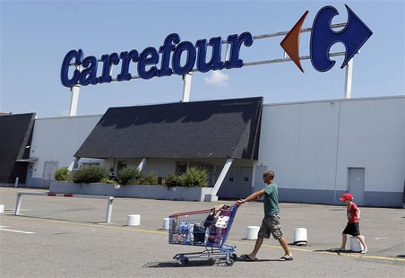 A customer pushes a shopping trolley as he leaves the Carrefour hypermarket in Brive-La-Gaillarde, central France, July 8, 2013. REUTERS/Reg
