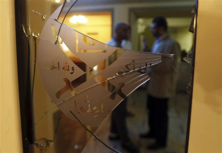 Members of the Muslim Brotherhood speak behind a door with shattered glass at the Muslim Brotherhood headquarters, which was attacked two da