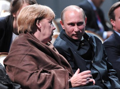 "Russian President Vladimir Putin (R) and German Chancellor Angela Merkel talk as they watch a fragment from the ballet ""Ruslan and Lyudmila"""