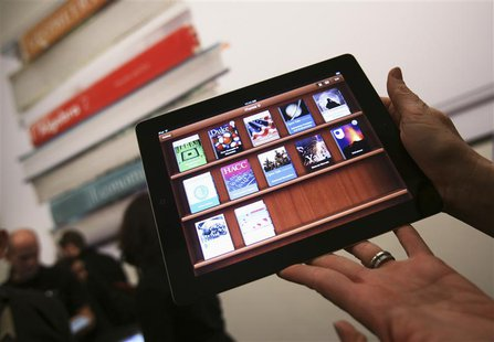A woman holds up an iPad with the iTunes U app after a news conference introducing a digital textbook service in New York in this January 19