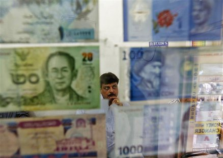 A man watches television inside his currency exchange shop in New Delhi August 30, 2013. REUTERS/Mansi Thapliyal
