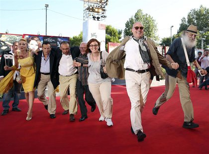 "Director Gianfranco Rosi (2nd R) poses with his cast during a red carpet for the movie ""Sacro Gra"" at the 70th Venice Film Festival Septembe"