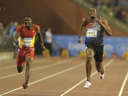 Usain Bolt of Jamaica (R) runs next to Justin Gatlin of the U.S. on his way to win the men's 100 metres during the IAAF Diamond League athle